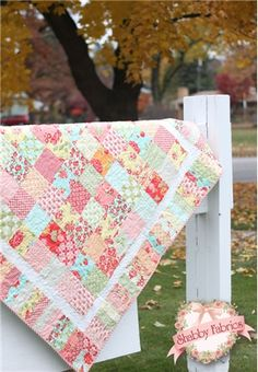 """Summertime Charm Pattern: Celebrate sunshine and color with the Summertime Charm Quilt!  This pattern shows you how to make this adorable 54 1/2"""" square quilt which can be used as a table topper, picnic blanket or wall hanging .This is a great choice for beginners because it's quick and easy using pre-cut charm packs and jelly rolls!"""