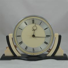 Made of cream and black plastic in an instantly Art Deco recognisable shape, this is an English Smiths mantel clock of the 1930's. Description from clockprops.com. I searched for this on bing.com/images