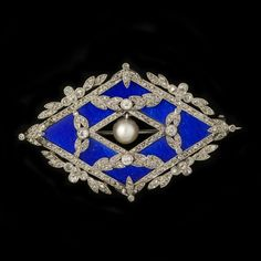 """GARLAND STYLE BROOCH LE SACHÉ  Country:  France Period:  Belle Epoque  A platinum lozenge shaped brooch signed """"Le Saché"""" in garland style. Enamelled in translucent blue and set with small brilliant cut diamonds and centering an oriëntpearl."""