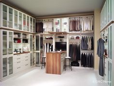 Custom walk in closet with frosted glass cabinet door insets, open clothes racks and even a desk area. All from NOLA Closets! We're so much more than closets.