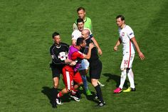 Blerim Dzemaili of Switzerland and Grzegorz Krychowiak of Poland are separated by match officials after the UEFA EURO 2016 round of 16 match between Switzerland and Poland at Stade Geoffroy-Guichard on June 25, 2016 in Saint-Etienne, France.