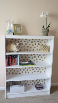 Design Tip: Gold foil polka dot wrapping paper to line the back of the bookcase - so chic!