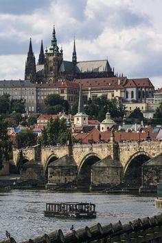 Prague boat, bridge and castle - View of boat on Vltava River, Charles Bridge and Prague Castle