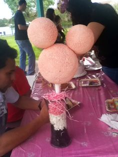 DIY birthday party center piece  spray paint some styrofoam balls glue them in a Minnie Mouse position put it on a stick place it in a vase throw some fringed confetti in the bottom at a bow and bam!!! Fun and cute decor for a girl bday party!!!!