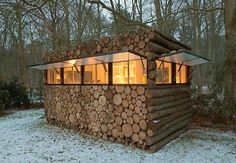 The 'logs' are merely a wood building facade covering a prefabricated plastic and steel frame. The 'cabin' is actually a recording studio for now, but would work just well as a mobile forest home.  When the window coverings are closed the cabin appears to be a stack of logs.