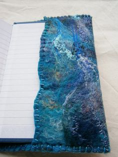 This is a handmade wet felted notebook cover made with merino tops and lots of embellishment fabrics and fibres. The edges are hand-sewn with blanket stitch. The edges of the inside flaps have been left natural and uncut, and have also been blanket stitched. You will receive the cover and the notebook inside. The notebook inside has lined pages. It is a standard A6 size, so it can be replaced with a similar notebook and used again. The overall size is 17 x 11.5 cm (roughly 6 1&#x2F...