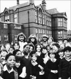 Robin Gibb with The Bee Gees outside their old school in Manchester
