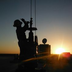 a roughbeck in  the oilfield at sunset