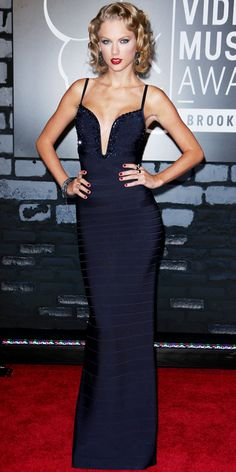 Swift posed in plunging embellished Herve Leger by Max Azria column. Her vampy retro-glam look was completed with select accessories, including drop earrings, bracelets and a cocktail rings.