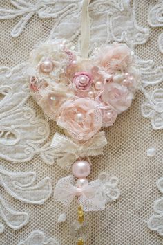 This listing is for one beautiful handmade ribbon work heart ornament by Jennelise Rose. This heart is trimmed around the edge with beautiful ivory lace trim and hangs from an ivory silk ribbon. Made with handmade flowers in pale pink velvet, pink tulle, pink and ivory lace, and dyed ribbons. It also is embellished with pearls, beads, and crystals and has a gorgeous chandelier crystal hanging from the base. This is a one of a kind piece! Heart measures 3 1/4 wide and with the ribbon and ...
