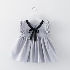 This dress is a trendy variation on the classic sailor style. Soft flutter sleeves, front bow detail and zip closure back, this dress is cool and comfortable f