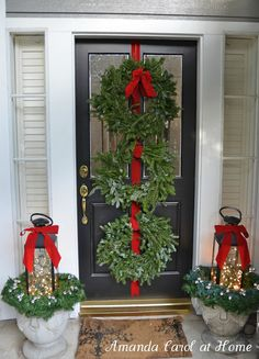 Front Porch Christmas Decor. 3 wreaths hung on door, lanterns filled with white lights and placed on urns filled with greenery.