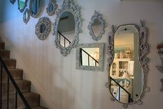 mirrors on a staircase wall, love this more than photos, we aren't photo people