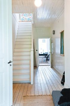 Swedish summer house entry; love the stark white walls; bleached floors + white stairs + ceiling