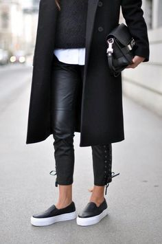Black coat + black sweater + white shirt layered underneath + coated jeans + slip ons