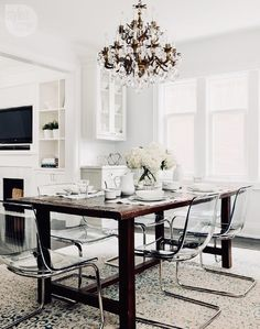 Create the perfect dining setting with a rustic wooden table paired with clear acrylic ghost chairs.