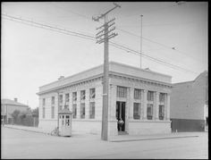 Exterior view of the Bank of New Zealand, Sydenham, Christchurch, showing young boy in bank doorway and Lawson Street with a bicycle leaning against a public telephone booth Adam Henry, Nz History, Christchurch New Zealand, Telephone Booth, Canterbury, Doorway, Public, Bicycle, Exterior