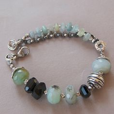 Chunky peruvian opals and black spinel are interspersed with sterling silver and fine silver. The blue-green opal rondelles are all natural stones with soft black and brown markings giving them a very organic look that pairs well with the artisan silver in this bracelet. A chunky sterling