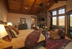 Lynne Barton Bier The fir trusses and stone fireplace create a cozy feeling in this inviting master bedroom..