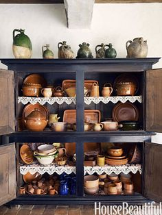 Local earthenware is displayed in an armoire with shelves lined in delicate lace.