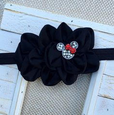 Quantity (1)    Black Chiffon Headband adorned with a Minnie Mouse center stone.  Attached to a black stretchy headband (more options available).  The flower measures approximately 5 inches and the center stone measures approximately 1 inch.    **Please use the drop down box to pick your hardware and/or choose your headband size**    *****************  In order to provide the best customer service possible, I ask that you please read my policy page. Here you will find information on our…