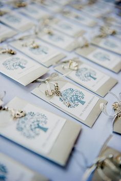 Elegant escort cards featuring silver cardstock, romantic illustrations, and beaded keys. |   Photo by Elizabeth Davis Photography
