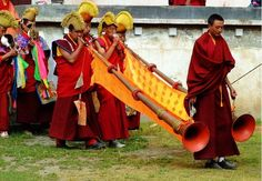 These long horns played by the monks are called Dungchen in Tibetan language. As it is too long and also a little heavy, the players need an assistant to hold it when moving forwards. Dungchen is an integral part of many forms of Tibetan ritual music and usually played in Tibetan Buddhist ceremonies. It is often played in pairs or multiples. It sounds like the singing of an elephant.