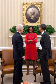 President Barack Obama and Vice President Joe Biden talk with First Lady Michelle Obama in the Oval Office.