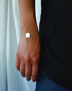 Disk Initial Bracelet by Olive Yew. Petite sterling silver circle disk is hand stamped with the letter of your choice.