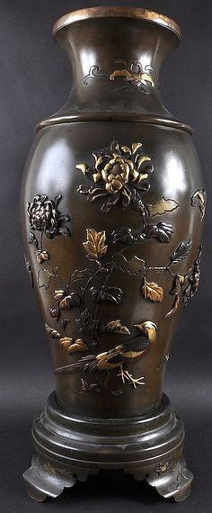 Description: A GOOD 19TH CENTURY JAPANESE MEIJI PERIOD BRONZE VASE ON STAND decorated in gold, mixed metals and other depicting birds amongst foliage and in flight. Few inlay losses. 2ft 4ins high.