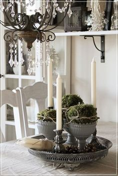 Give a more organic and natural look to your centerpiece by adding plants and pinecones into your vase arrangement. White candles also bring a sense of tranquility into the overall designs.