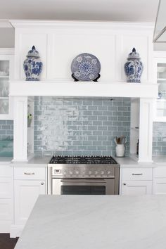 Marble and white Kitchen ,blue and white ceramics, range hood, custom cabinetry, ilve cooker, nickel door hardware, nickel pendant light, blue subway tiles, marble bench top - Melinda Hartwright Interiors