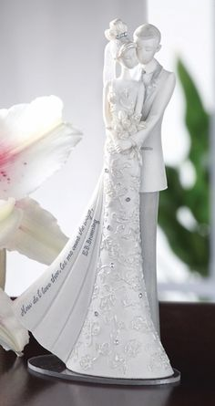 """Wedding Cake Topper 6.25""""H, Weight 6oz., Resin and Stone mix. Embellished with rhinestones and a fabric tulle veil. Love quote on bride's dress.  Literary caption: How do I love thee let me count the ways. -E.B. Browning."""
