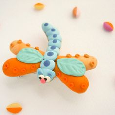 Colourful Dragonfly brooch hand sculpted in blue and orange polymer clay. £10.49, via Etsy.