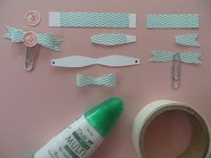 You need a three inch strip and 2 inch strip of 1/2 CS strips with the Tape It image stamped in center.  Fold then in half and free cut them as shown. glue dots to adhere the back part of the ribbon to the paper clip - the glue dot peeks through the paper clip, sticking to the ribbon body.  Use glue dot to stick on the button from Notable Notions set stamped in Calypso coral and punched out using 1/2 circle punch.