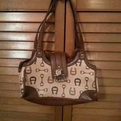 NWOT Etienne Aigner Handbag Logo design in brown, beige and tan with decorative silver buckle at magnetic clasp.  Three same size pockets with side zipper in middle.  This small gem is spotless and in EXCELLENT condition!!! Bags Mini Bags