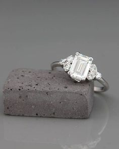 ✿ THE JEWEL Handmade solid 14k white gold emerald cut engagement ring set with Moissanite and diamonds. A brilliant and alluring Emerald Cut engagement ring, set with Charles & Colvard Forever One Moissanite and complemented with 6 surrounding diamonds. An elegant engagement ring that will #DazzlingDiamondEngagementRings