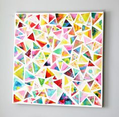 let students paint paper with watercolors, wet on wet, similar colors. Let dry and cut into triangles. Students pick triangles and glue down randomly, leaving white around each one. Maybe try with black or other color background?