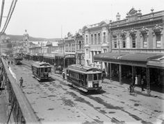 Trams travelling along Victoria Avenue, Wanganui. The storefronts of Markham & Shewan, Thomas Warnock and William Rees-Jones can be seen. Taken by Frank J Denton in New Zealand North, Kiwiana, Maui, Old Things, Street View, Travelling, Victoria, Island, History