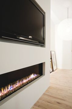 Centrepiece wall in the living room that containing a fireplace and a flat screen.