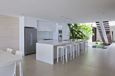 This tropical, open design home mixes indoor and outdoor spaces freely, with a kitchen standing next to a garden pool with open air access. Large minimalist white island features sink and space for five diners, while matching white cabinetry contrasts with beige wall and floor tiling.