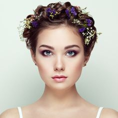 Face of beautiful woman decorated with flowers - Face of beautiful woman decorated with flowers. Perfect makeup. Beauty fashion. Eyelashes. Cosmetic Eyeshadow