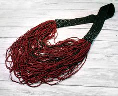 This knitted multi strand necklace, in bordeaux red and black colors, was handmade with:  -hand crocheted strings (bordeaux red polyamide) -hand crocheted strings (black viscose with gold mettalic insertions) -hand knitted tube strings (bordeaux red polyamide) -black textile strap -graphite seed beads  This necklace is soft and comfortable to wear and surely makes a statement! This versatile accessory can be wear over a t-shirt, under your suit jacket or blazer, over a turtle neck or with a…