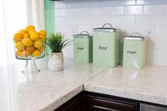 As seen on HGTV's Renovation Raiders, this kitchen's rich, dark cabinetry offsets the white quartz countertops and white subway tile backsplash. Sugar and flour containers in soft green add a touch of color to this classic yet updated space.
