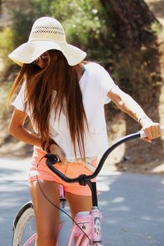 Riding a bike in a floppy hat and neon coral shorts. Neon coral is my new favorite color. #splendidsummer