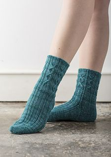 Neat little cables, flowing seamlessly from cuff to heel and along the front of the foot, decorate these attractive socks. We love the yarn choice, too: the Dream in Color Starry not only has a thread of Lurex running through it for a touch of sparkle, but it also has a subtle marled effect which complements the cable stitches beautifully.
