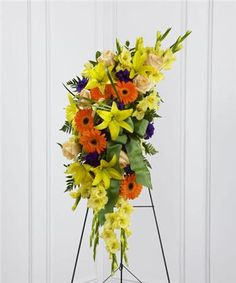 Sunny yellow gladiolus and Asiatic lilies are offset by crème de la crème roses, orange gerbera daisies, purple lisianthus, green button poms and lush greens. Accented with a designer sea mist green wired taffeta ribbon and displayed on a wire easel, this beautiful standing spray will be a ray of light to honor the deceased and bring comfort to friends and family.
