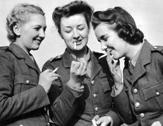 Three women of the British ATS light up a cigarette together in 1939. ATS regulations forbid smoking when soldiers are wearing their hats.