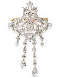 PLATINUM, GOLD AND DIAMOND BROOCH, CIRCA1900    Of openwork design suspending diamond fringes, set with numerous old mine, old European and single-cut diamonds weighing a total of approximately 12.75 carats, fitted with retractable pendant loop.