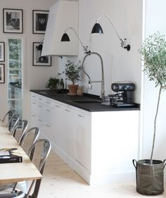 White kitchen with black countertop, no upper cabinets, wall built in accent lights, medium sized drawer pulls.